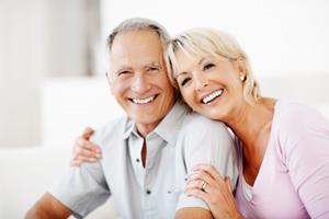 Cheerful mature woman embracing senior man against white